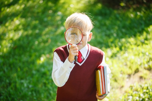 Portret kleine schooljongen op de natuur. kind met boeken en loep. onderwijs voor kinderen. terug naar school-concept