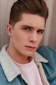 Portret knap mannelijk ernstig gezicht met schone gezonde huid met modieus kapsel. stijlvolle sexy aantrekkelijke man in blauwe denim vintage jasje buitenshuis. detailopname.
