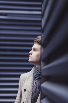 Portret knappe mode mannelijk model man gekleed in een elegante jas poseren in de buurt van blauwe muur