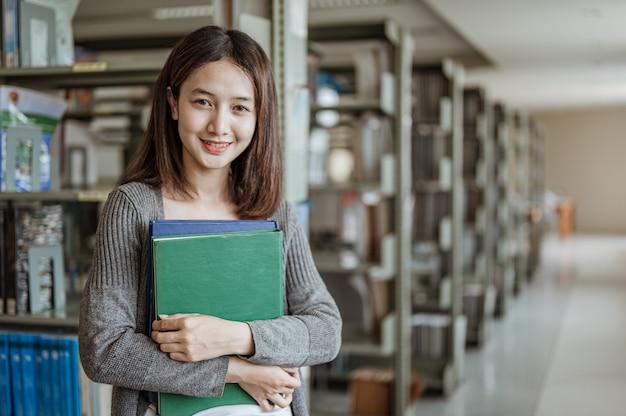 Portret lachende aziatische vrouw die achter haar staat is een boekenplank in een universiteitsbibliotheek. onderwijs, school, bibliotheek en kennis concepten.