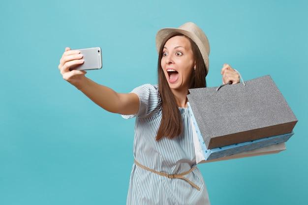Portret lachende vrouw in zomerjurk, stro hoed met pakketten tassen met aankopen na het winkelen doen selfie schot op mobiele telefoon geïsoleerd op blauwe pastel achtergrond. ruimte voor advertentie kopiëren