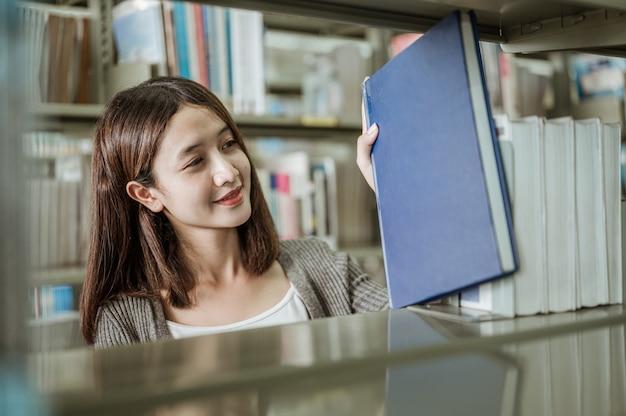 Portret lachende vrouw pakte gelukkig een boek van een boekenplank in een universiteitsbibliotheek. onderwijs, school, bibliotheek en kennis concepten.