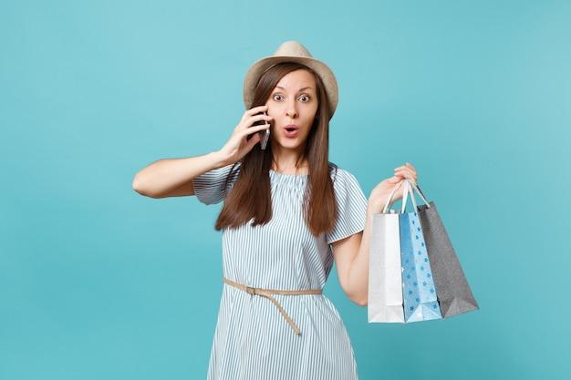 Portret leuke lachende vrouw in zomerjurk, stro hoed met pakketten tassen met aankopen na het winkelen, praten op mobiele telefoon geïsoleerd op blauwe pastel achtergrond. kopieer ruimte voor advertentie.