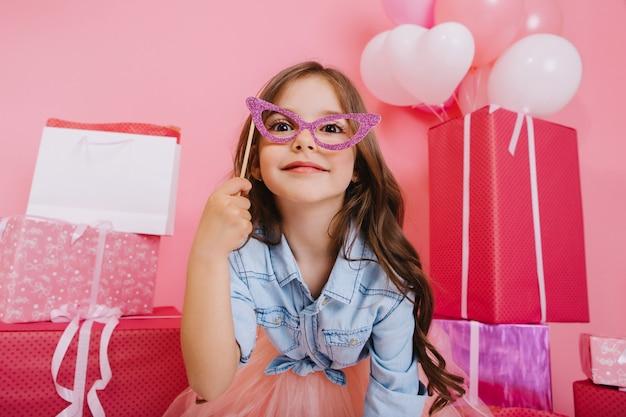 Portret lief klein meisje met lang donkerbruin haar met masker op gezicht, op zoek naar camera op geschenkdozen, ballonnen, roze achtergrond. mooi opgewonden kind plezier, verjaardagsfeestje vieren