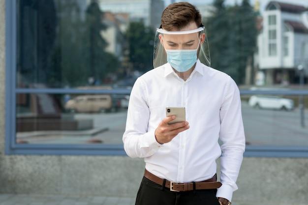 Portret man met masker met behulp van mobiel
