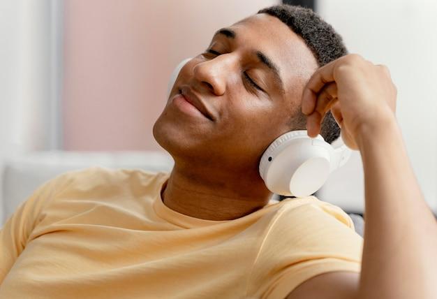Portret man thuis ontspannen terwijl het luisteren naar muziek