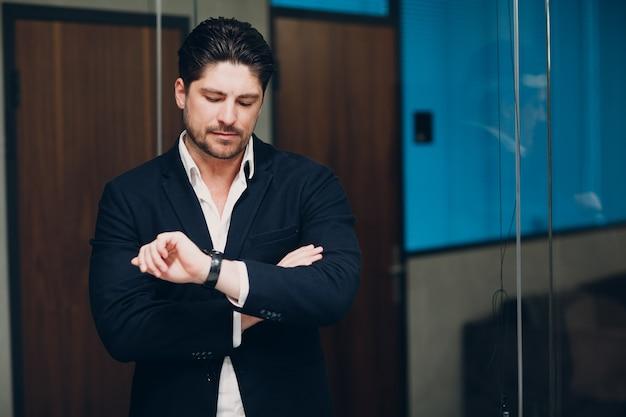 Portret man zakenman in zwart pak kijk horloge in kantoor
