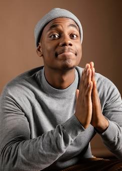 Portret mannetje dat glb met het bidden teken draagt