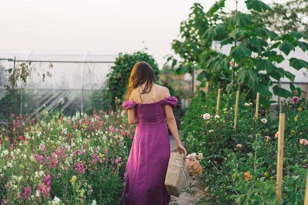Portret meisje met lang haar met een bloemmand. loop door de bloementuin. meisje en bloemen. floristiek.