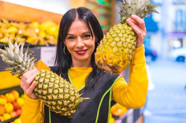 Portret met ananas in de hand van een donkerbruin kaukasisch fruitmeisje, werkzaam in een fruitwinkel