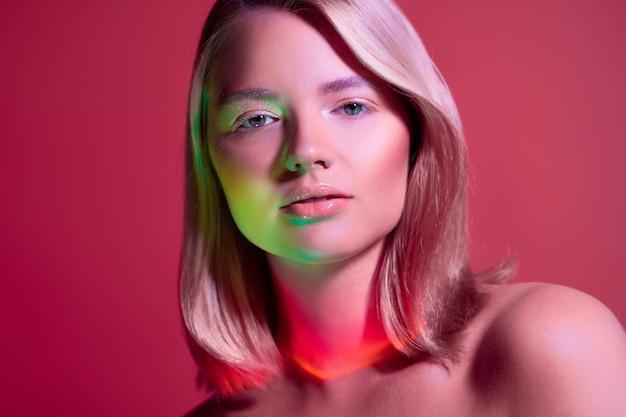 Portret met neonstijl verlichting van een jonge mooie blonde