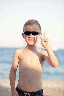 Portret met serieuze blonde kleine jongen in zonnebril die op het strand staat met een wazige achtergrond aan zee