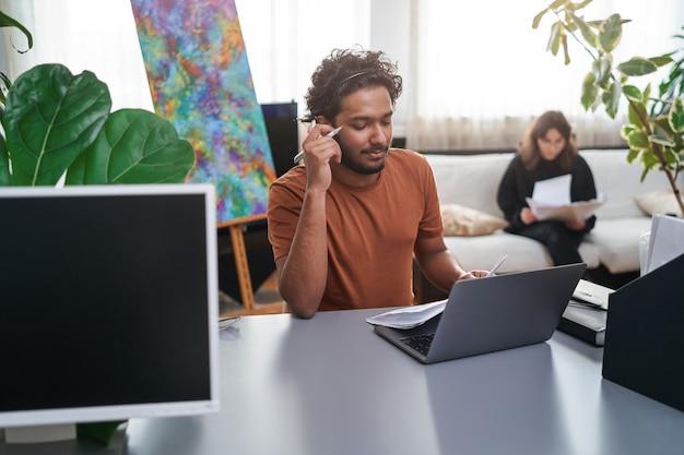Portret met warme sfeer van een serieuze indiase stylist met een laptop en concepten van shirts. mannelijke ontwerper en zijn kleine bedrijf.