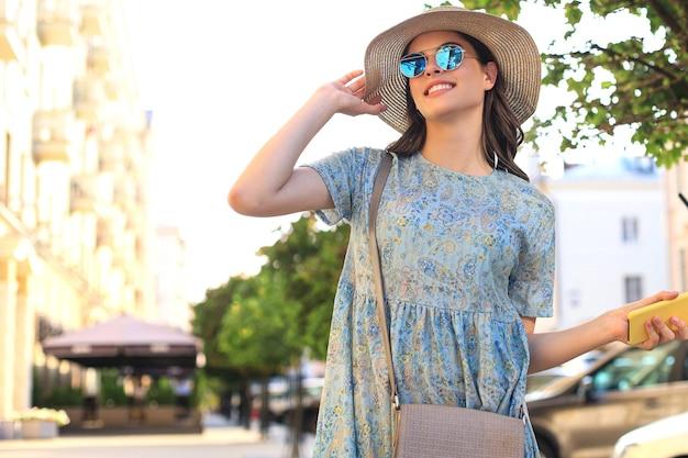 Portret mode vrouw in blauwe jurk in zonnebril lopen op straat en smartphone in haar hand houden.