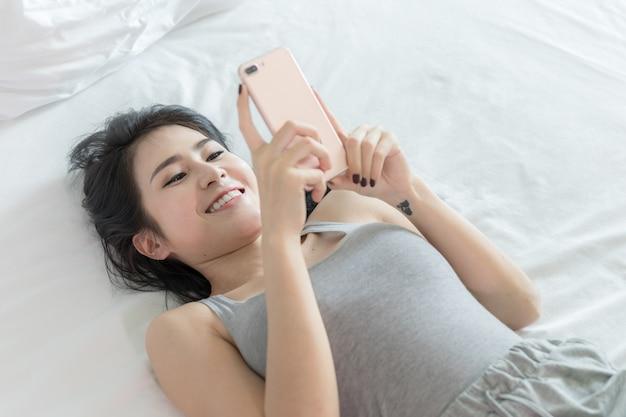 Portret model dame sexy slapen spelen slimme telefoon in de slaapkamer