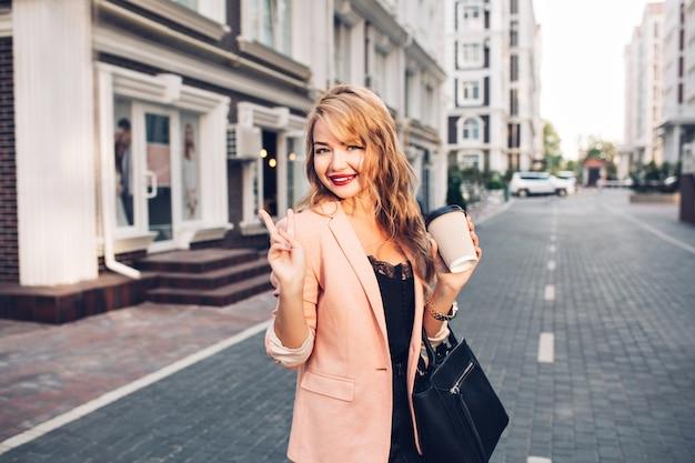Portret modieuze blonde vrouw met lang haar wandelen in koraal jasje op straat. ze houdt een kopje koffie vast