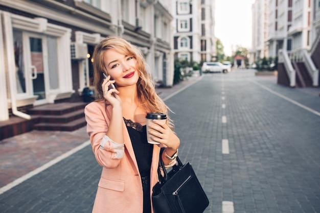 Portret modieuze blonde vrouw met lang haar wandelen in koraal jasje op straat. ze praat aan de telefoon, houdt een kopje vast