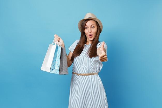 Portret modieuze lachende mooie blanke vrouw in zomerjurk, strohoed met pakketten tassen met aankopen na het winkelen geïsoleerd op blauwe pastel achtergrond. kopieer ruimte voor advertentie.