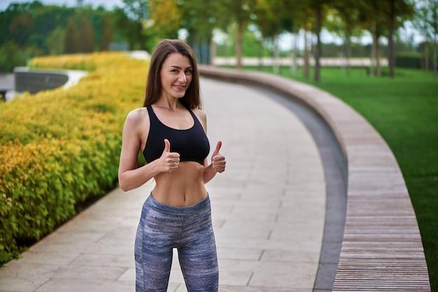 Portret mooi actief meisje die en duim-omhooggaand gebaar in het park glimlachen tonen.