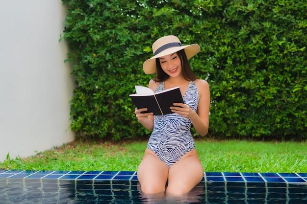 Portret mooi jong aziatisch vrouw gelezen boek rond zwembad