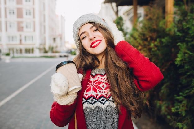 Portret mooi meisje in een rode jas en gebreide muts lopen op straat. ze houdt koffie voor onderweg vast in witte handschoenen en lacht vriendelijk met rode lippen.
