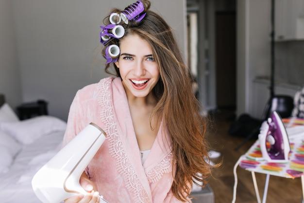 Portret mooi meisje in roze badjas met krullen op hoofd thuis. ze houdt een föhn vast, glimlachend.