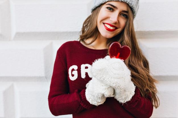 Portret mooi meisje in witte handschoenen op grijze muur. ze draagt een gebreide muts, marsala-trui, houdt hartlolly vast en lacht.