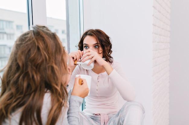 Portret mooi meisje met krullend haar in pyjama, het drinken van thee op venster in lichte kamer. ze ziet er verbaasd uit als het meisje voor de deur staat.