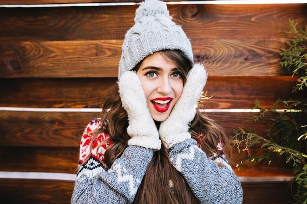 Portret mooi meisje met lang haar en rode lippen in gebreide muts op houten. ze raakt haar gezicht in warme handschoenen aan, glimlachend.