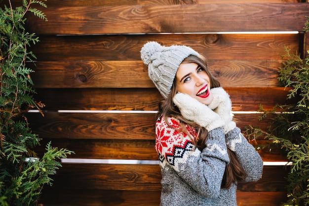 Portret mooi meisje met lang haar in gebreide muts en winter trui op houten. ze raakt gezicht met handen in handschoenen en glimlacht.