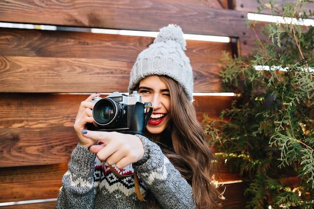 Portret mooi meisje met lang haar in gebreide muts met plezier bij het maken van een foto op camera op houten.