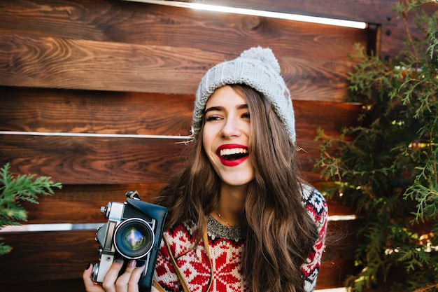 Portret mooi meisje met lang haar in gebreide muts met plezier met camera op houten.