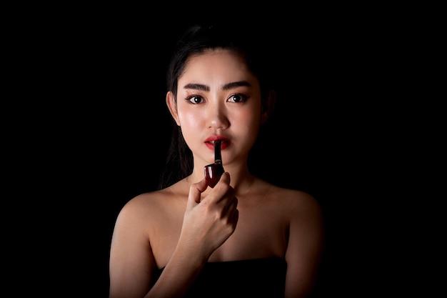 Portret mooie aziatische jonge vrouwen met een rookpijptabak op de zwarte achtergrond