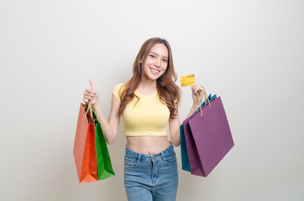 Portret mooie aziatische vrouw met boodschappentas en creditcard op witte achtergrond