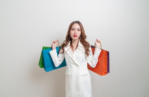 Portret mooie aziatische vrouw met boodschappentas op witte achtergrond
