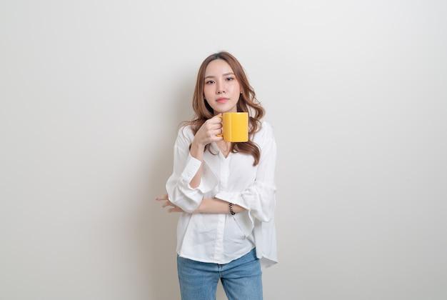 Portret mooie aziatische vrouw met koffiekopje of mok op witte achtergrond