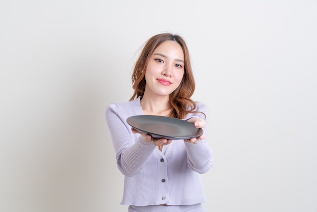 Portret mooie aziatische vrouw met lege plaat op witte achtergrond