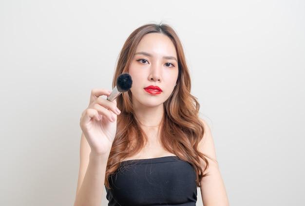 Portret mooie aziatische vrouw met make-up borstel op witte achtergrond
