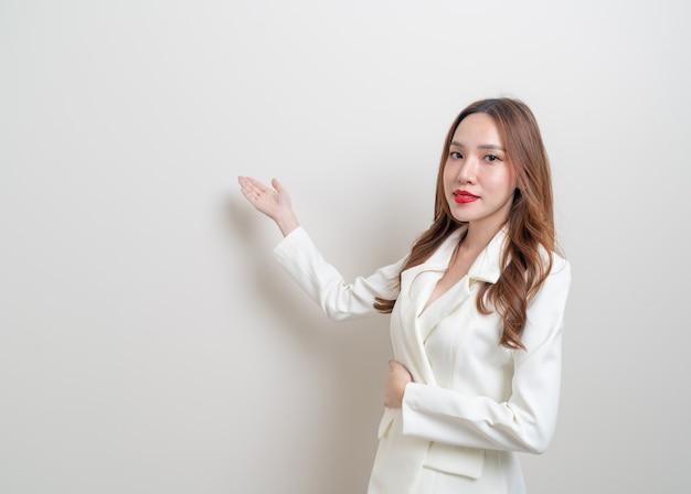 Portret mooie aziatische zakenvrouw met hand presenteren of wijzen op witte achtergrond