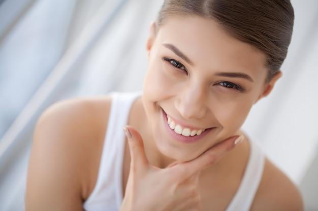 Portret mooie gelukkige vrouw met het witte tanden glimlachen