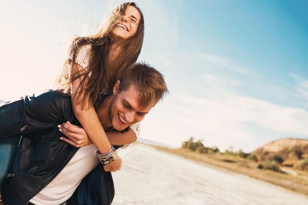 Portret mooie gezonde jonge volwassenen vriendin en vriendje gelukkig knuffelen. jong mooi paar in liefde die op de zonnige lente langs strand dateren. warme kleuren.