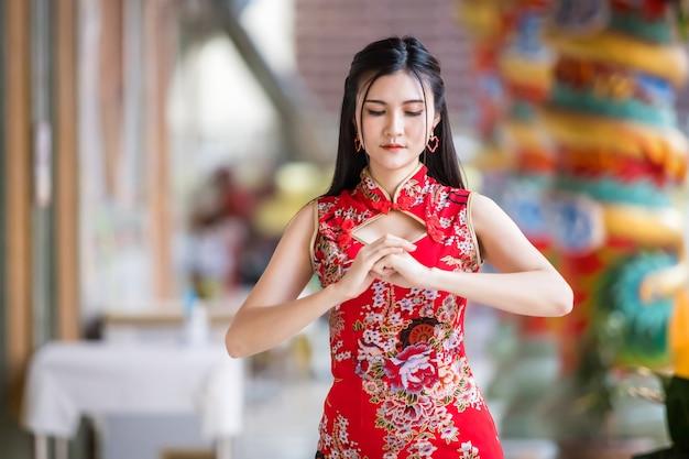 Portret mooie glimlach aziatische jonge vrouw, gekleed in rode traditionele chinese cheongsam, voor chinees nieuwjaar festival op chinees heiligdom