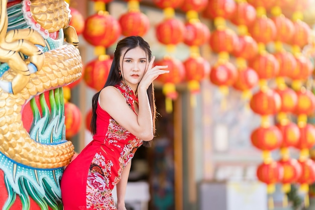 Portret mooie glimlach aziatische jonge vrouw, gekleed in rode traditionele chinese cheongsam