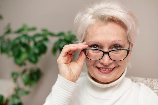 Portret mooie hogere vrouw met glazen
