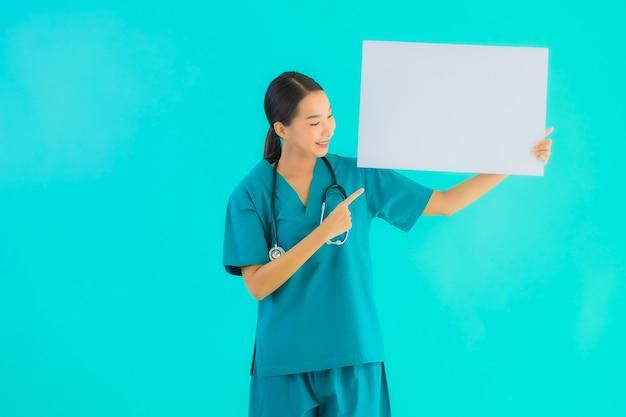 Portret mooie jonge aziatische artsenvrouw met leeg aanplakbiljet