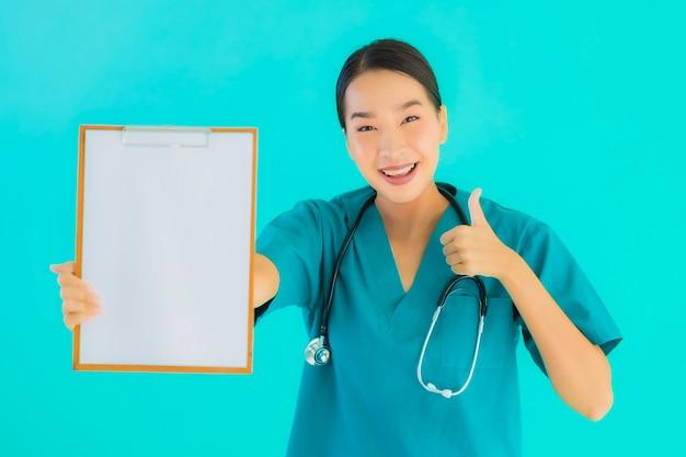 Portret mooie jonge aziatische artsenvrouw met leeg karton voor exemplaarruimte