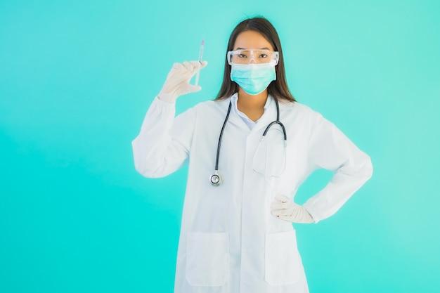 Portret mooie jonge aziatische artsenvrouw met vaccinspuit en drung of geneeskundefles