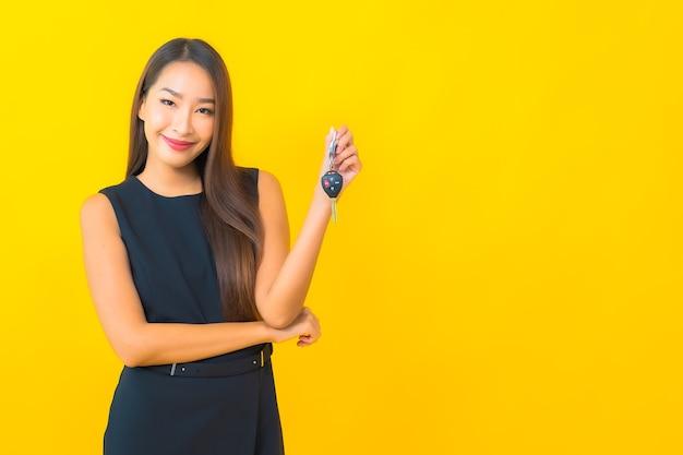 Portret mooie jonge aziatische bedrijfsvrouw met autosleutel op gele achtergrond