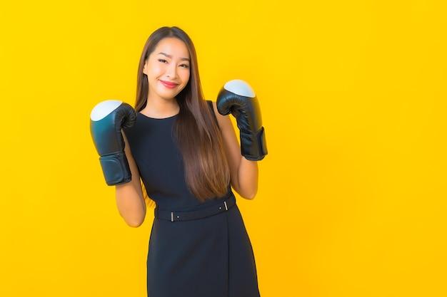 Portret mooie jonge aziatische bedrijfsvrouw met bokshandschoen op gele achtergrond
