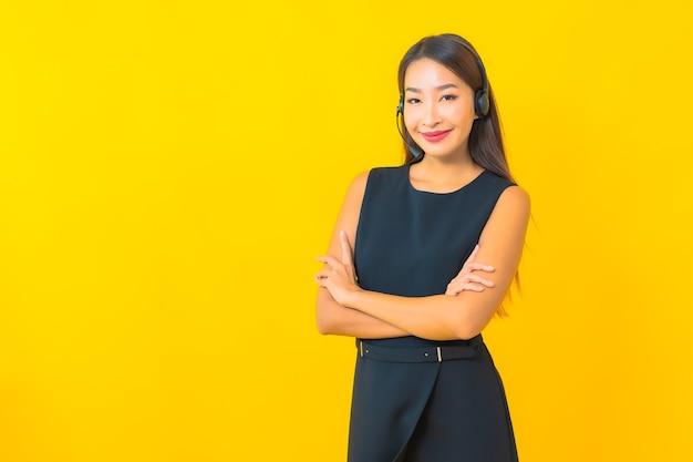 Portret mooie jonge aziatische bedrijfsvrouw met de klantenzorg van het hoofdtelefooncall centre op gele achtergrond